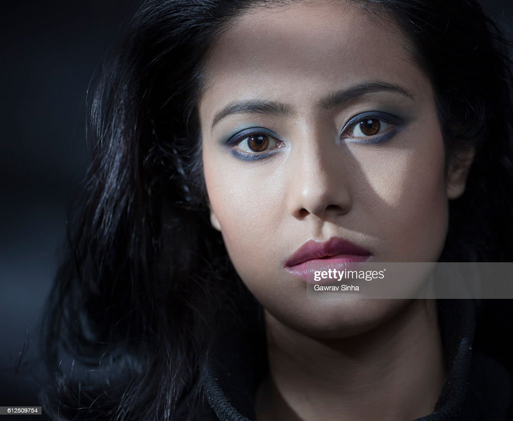 Beautiful serene young woman looking at camera with blank expression. : Stock Photo