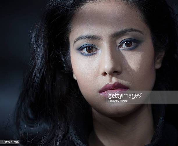 Beautiful serene young woman looking at camera with blank expression.
