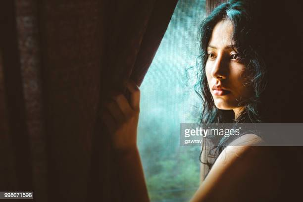 Beautiful serene young woman thinks near window.