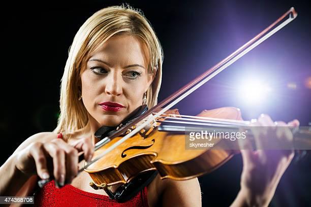 Beautiful serious woman playing violin.