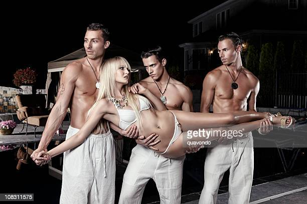beautiful sexy woman in bikini carried by shirtless handsome men - topless bikini models stock pictures, royalty-free photos & images