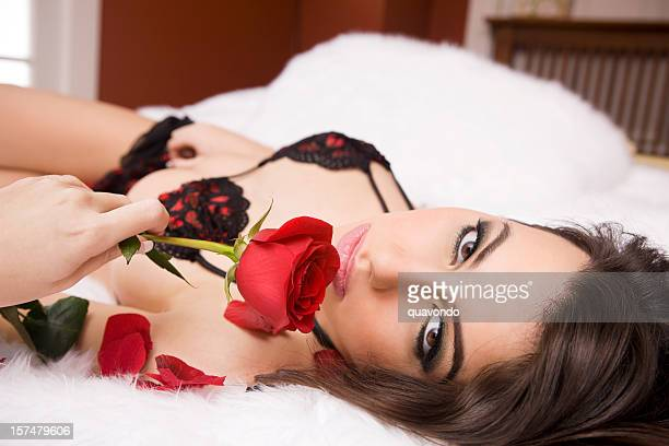 Beautiful Sexy Woman Lying on Bed in Lingerie Holding Rose