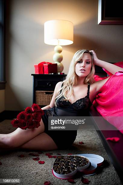 Beautiful Sexy Young Blond Woman in Black Lingerie, Roses, Chocolates
