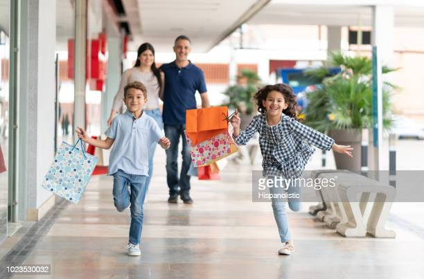 beautiful siblings having fun at the mall running and holding shopping bags - shopping mall stock pictures, royalty-free photos & images