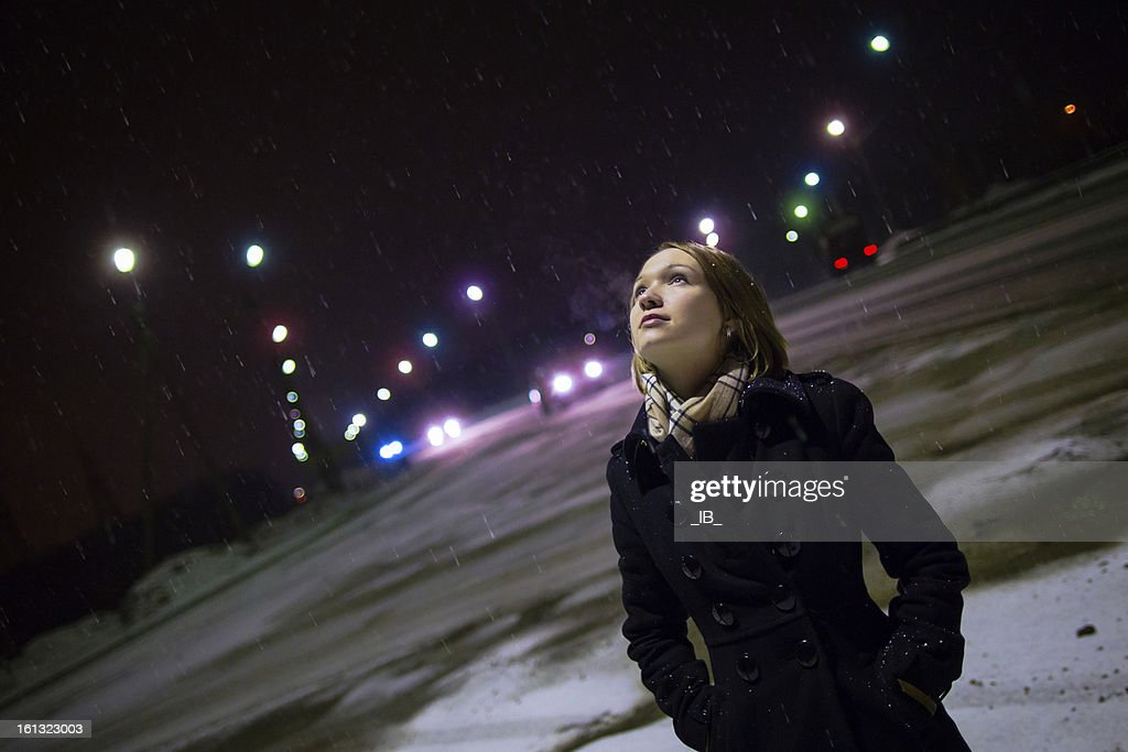 Beautiful single girl at night in the snow : Stock Photo