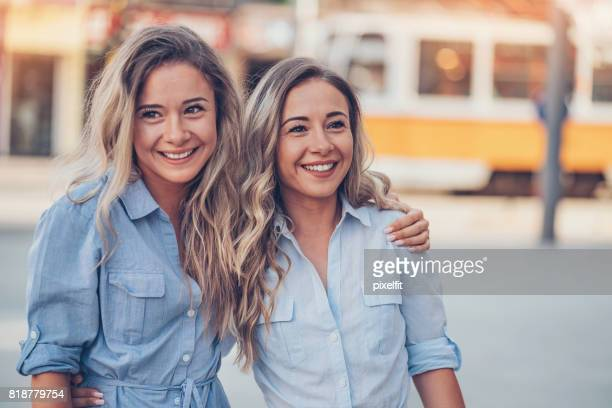 beautiful sisters walking in the city - sister stock pictures, royalty-free photos & images