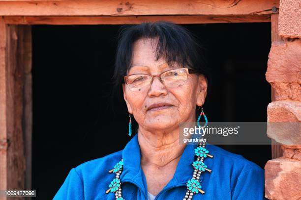 beautiful sixty five year old senior native american navajo woman posing inside an authentic hogan - 63 year old female stock pictures, royalty-free photos & images