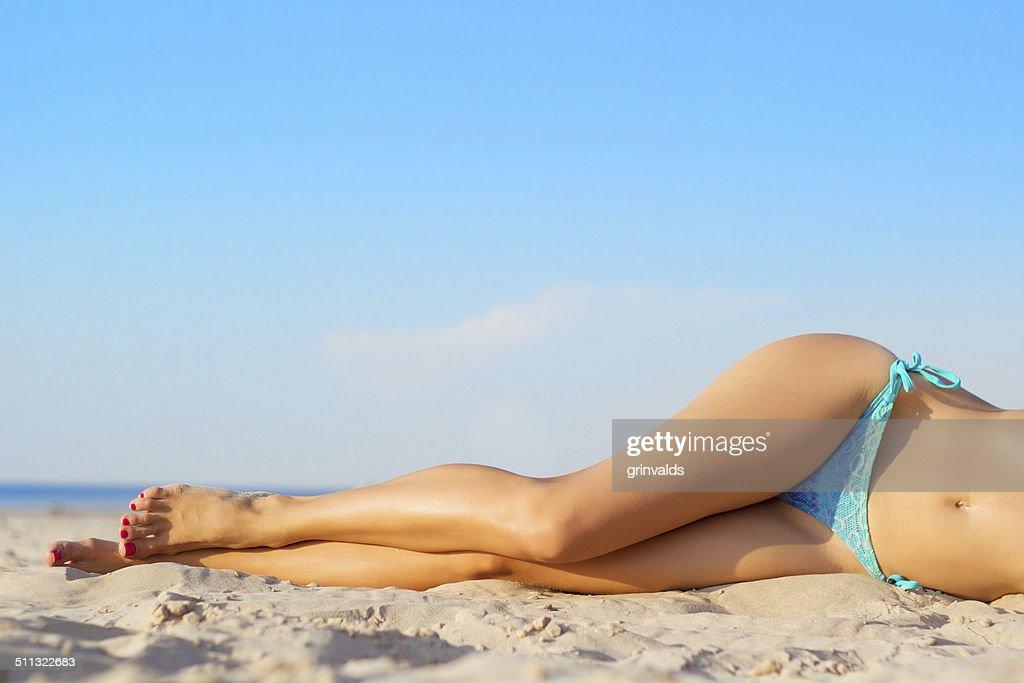 Beautiful slim women's legs on the beach