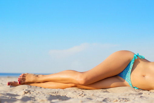 Beautiful slim women's legs on the beach