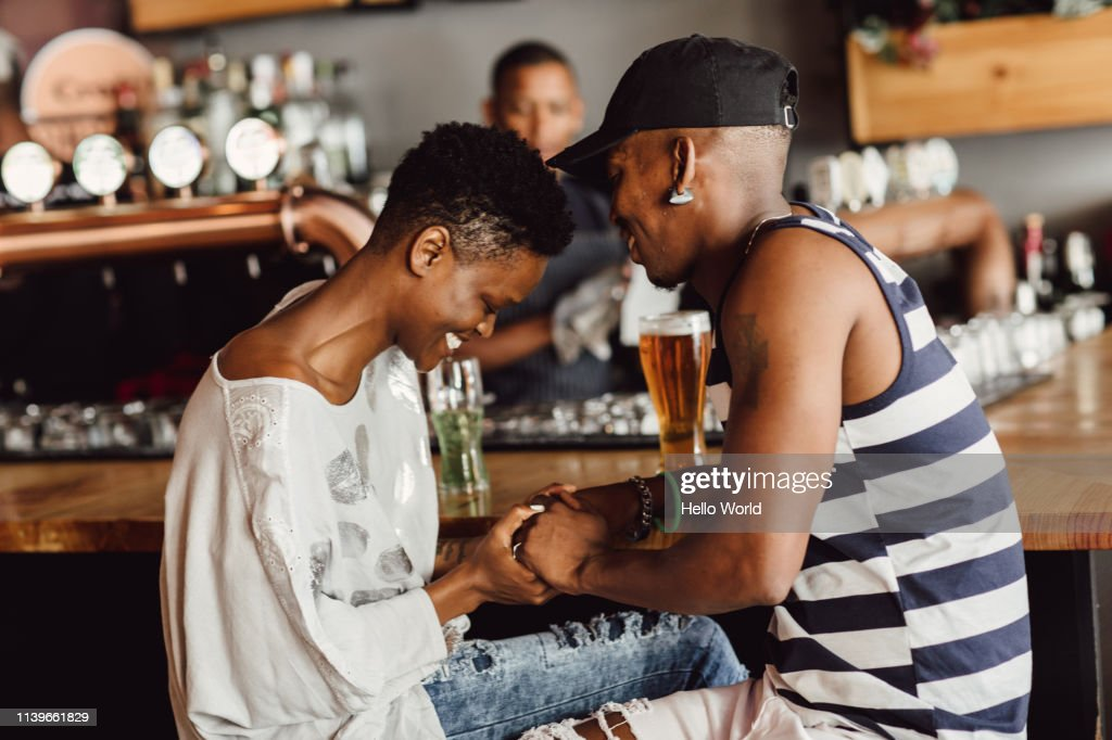 Beautiful smiling and affectionate couple holding hands whilst seated at bar drinking beer. : Stock Photo