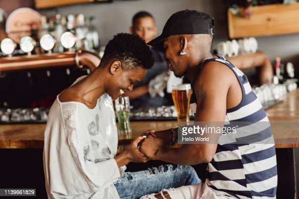 beautiful smiling and affectionate couple holding hands whilst seated at bar drinking beer. - dating stock pictures, royalty-free photos & images
