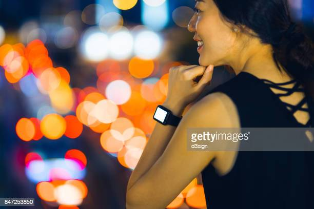 Beautiful smiling Asian lady with smart watch in illuminated city at night