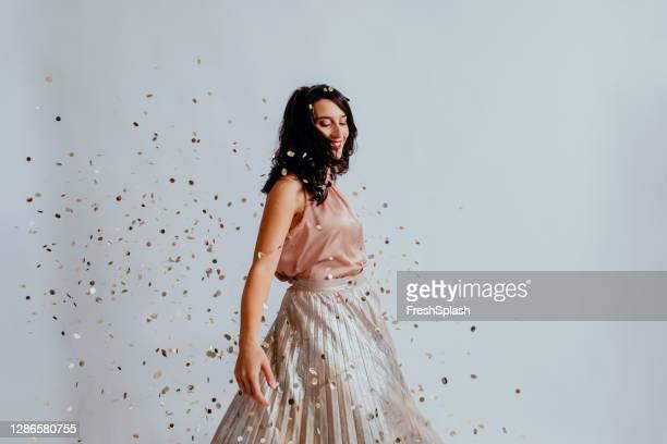belle femme noir-haired de sourire dansant sous des confettis dans une jupe élégante longue - jupe photos et images de collection
