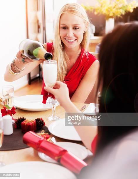 Beautiful smiling blonde pours champagne for friend at Christmas celebration