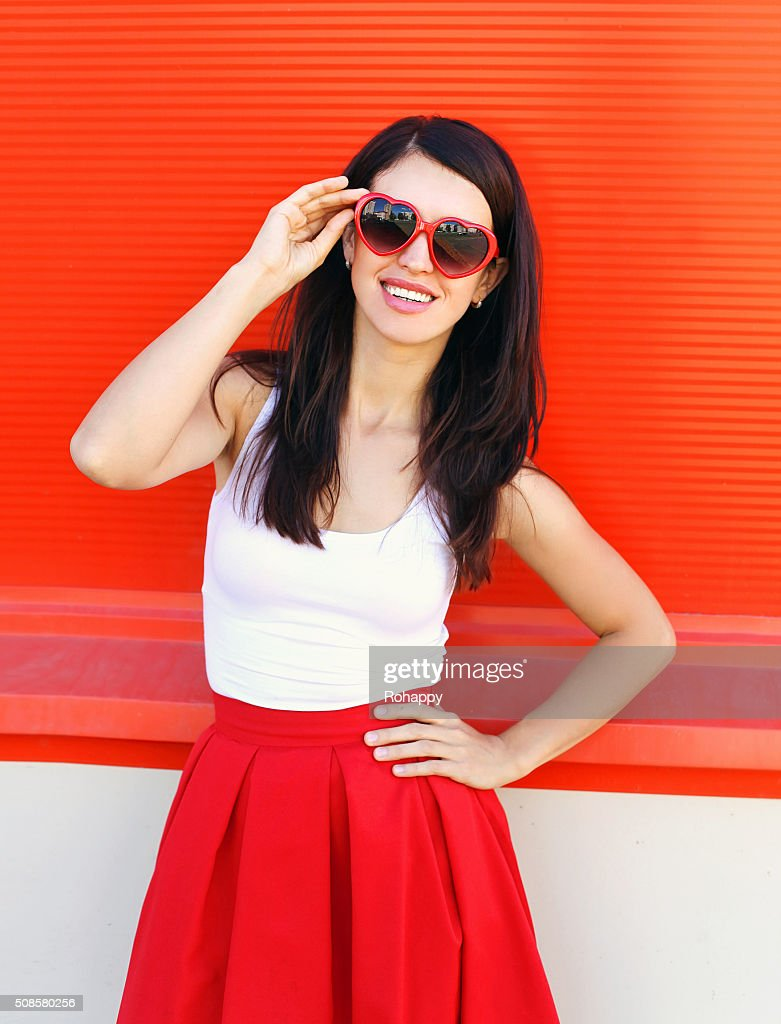 Beautiful smiling brunette woman wearing red sunglasses over colorful background : Stock Photo