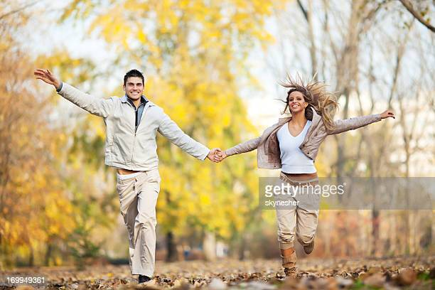Beautiful smiling couple running in the park.
