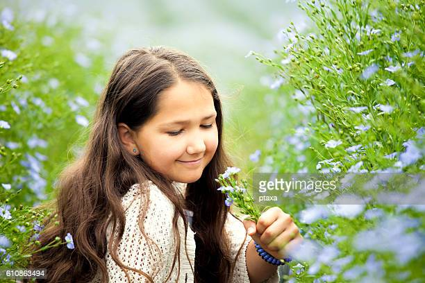 Beautiful smiling girl in a flax field