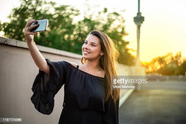 schöne lächelnde mädchen in schwarzem kleid - schwarzes kleid stock-fotos und bilder