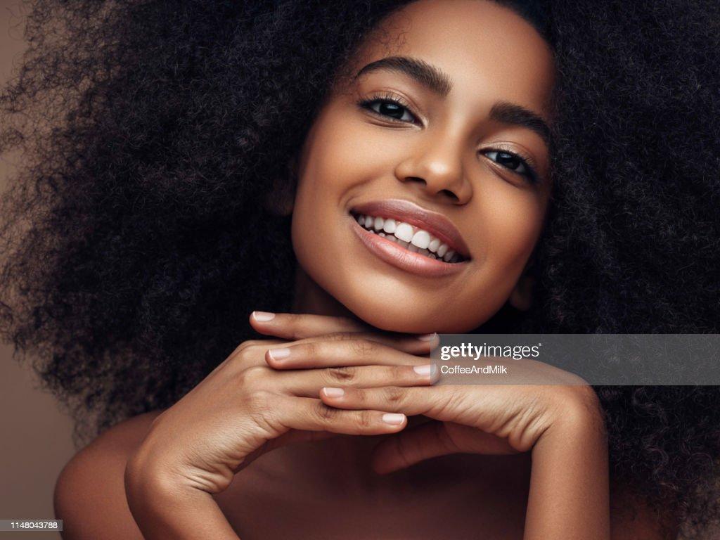 カーリーヘアスタイルを持つ美しい笑顔の女の子 : ストックフォト
