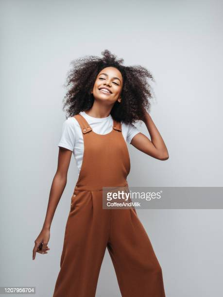 beautiful smiling girl with curly hairstyle - bib overalls stock pictures, royalty-free photos & images