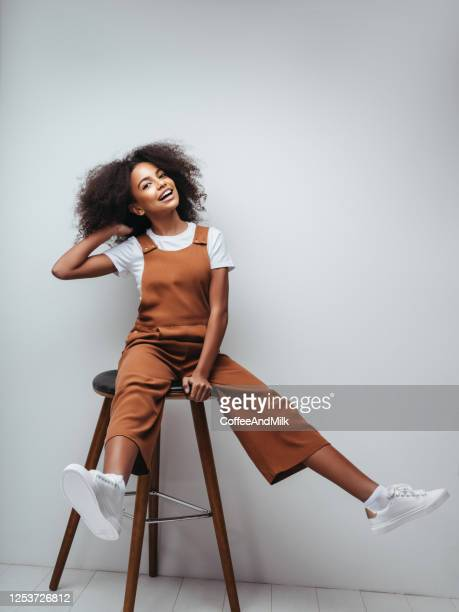beautiful smiling girl with curly hairstyle - dungarees stock pictures, royalty-free photos & images