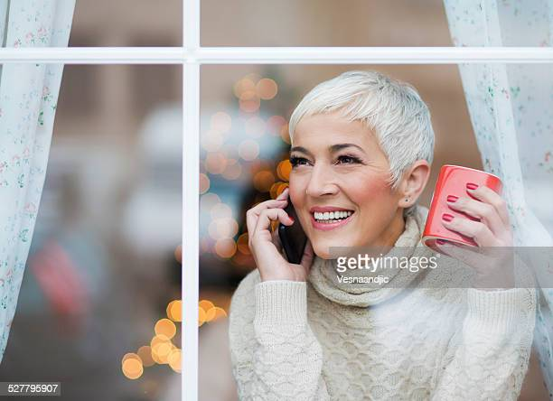 beautiful smiling mature woman looking through window - turtleneck stock pictures, royalty-free photos & images