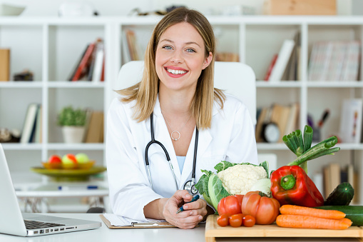 Beautiful smiling nutritionist looking at camera and showing healthy vegetables in the consultation. 1044382612