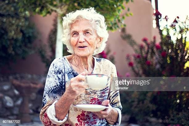 beautiful smiling senior woman drinking coffee in the morning - 80 89 jaar stockfoto's en -beelden