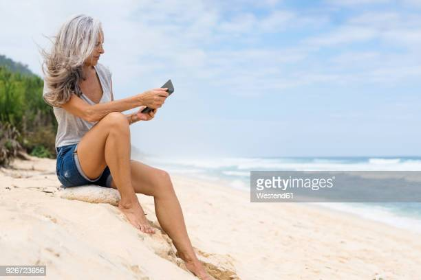 Beautiful smiling senior woman sitting at the beach, holding e-book