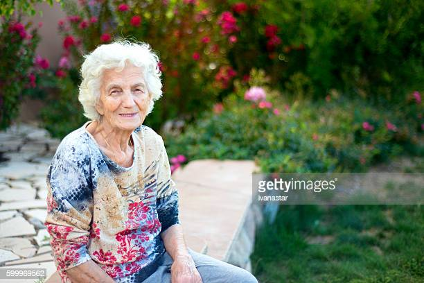 Beautiful smiling senior woman sitting in garden