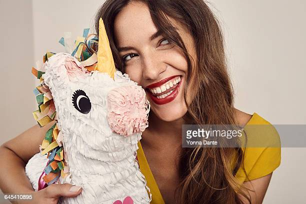 beautiful smiling woman holding a unicorn pinata