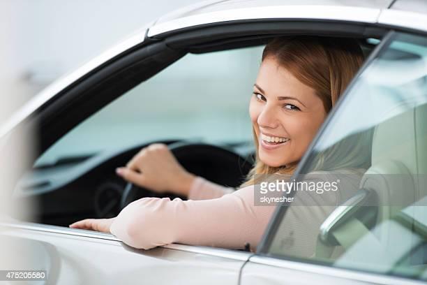 Beautiful smiling woman in a car looking at camera.