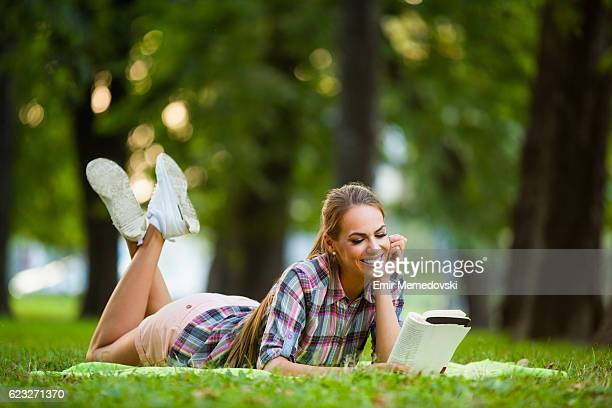 Beautiful smiling woman reading an interesting book in park.