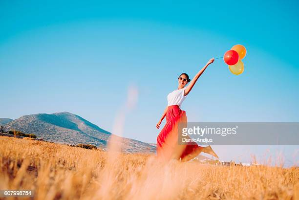beautiful smiling woman running threw the fields holding balloons