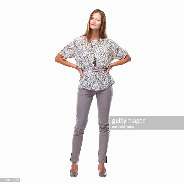 beautiful smiling woman standing with hands on hips against white background - handen op de heupen stockfoto's en -beelden