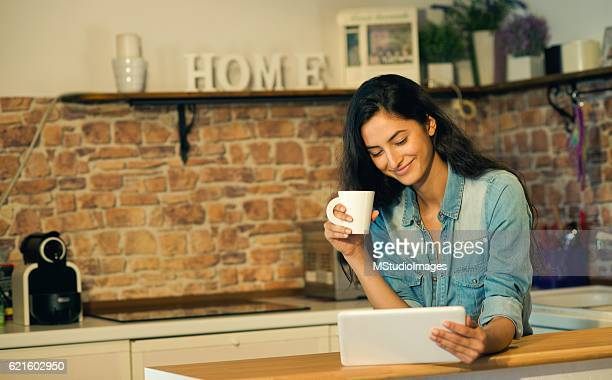Beautiful smiling woman using digital tablet at home.