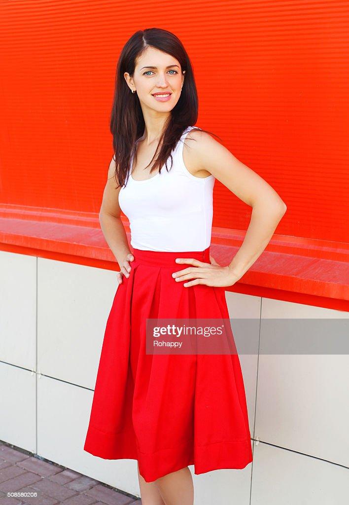 Wunderschöne lächelnde Frau mit einem roten Kleid über farbenfrohe Hintergrund : Stock-Foto