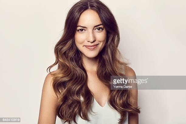beautiful smiling woman with long brown wavy hair - langes haar stock-fotos und bilder