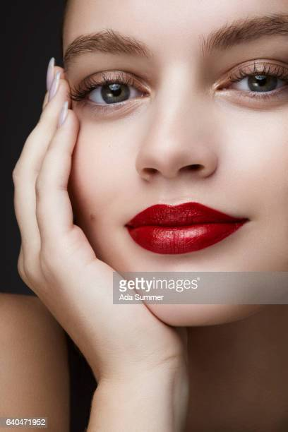 Beautiful smiling woman with red lips leaning on her hand