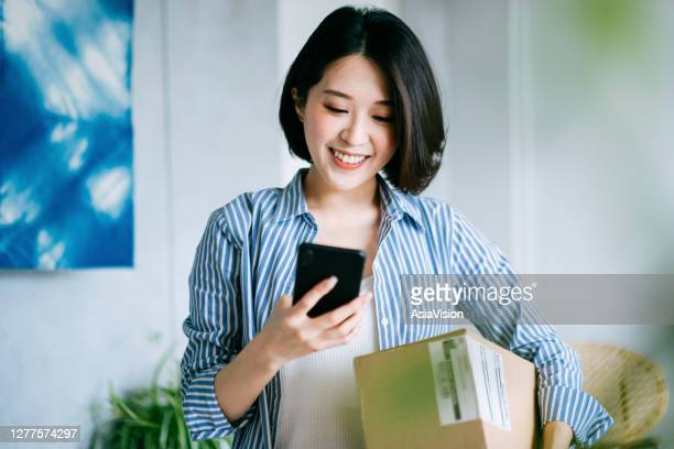 beautiful smiling young asian woman checking smartphone while receiving a parcel at home - returning merchandise stock pictures, royalty-free photos & images
