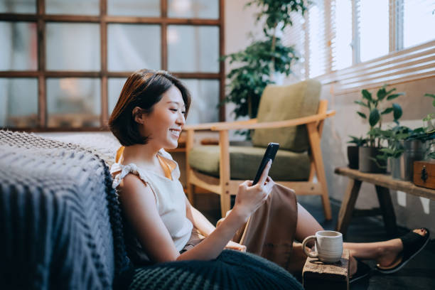 beautiful smiling young asian woman chilling at home, sitting on the floor in bedroom, enjoying a cup of coffee and using smartphone - talking on phone stock pictures, royalty-free photos & images