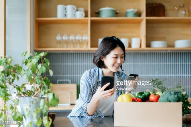 beautiful smiling young asian woman grocery shopping online with mobile app device on smartphone and making online payment with her credit card, with a box of colourful and fresh organic groceries on the kitchen counter at home - credit card stock pictures, royalty-free photos & images