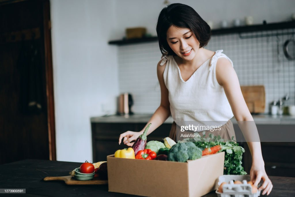 Beautiful smiling young Asian woman received a full box of colourful and fresh organic groceries ordered online by home doorstep delivery service. She is sorting out the groceries and preparing to cook a healthy meal : Stock Photo