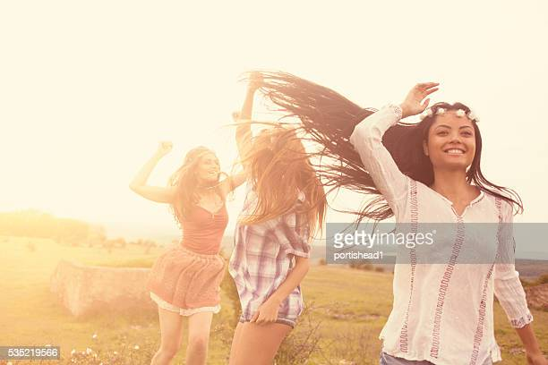 Beautiful smiling young hipster women dancing in the grassland