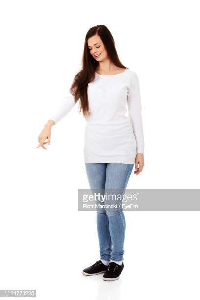 beautiful smiling young woman gesturing over white background - 下を向く ストックフォトと画像
