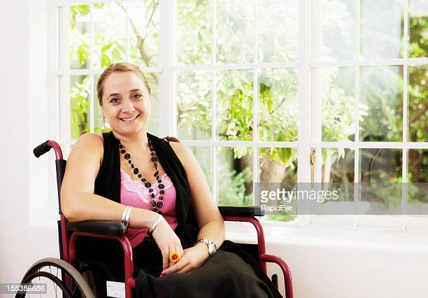 Beautiful smiling young woman in wheelchair by window