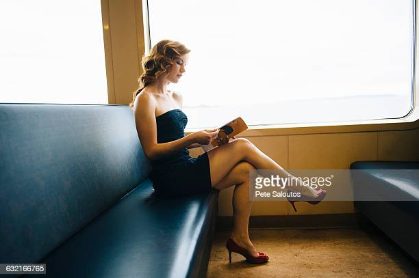 beautiful sophisticated woman reading magazine on ferry crossing, seattle, usa - mini dress stock photos and pictures
