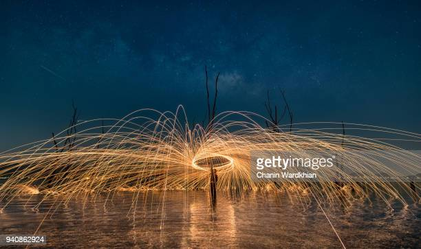 A beautiful spinning steel wool in the great reservoir in Thailand along with the stars