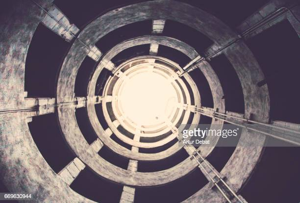 Beautiful spiral geometric shape created by a parking ramp in a decay architecture building with nice vanishing point and vertigo feeling.