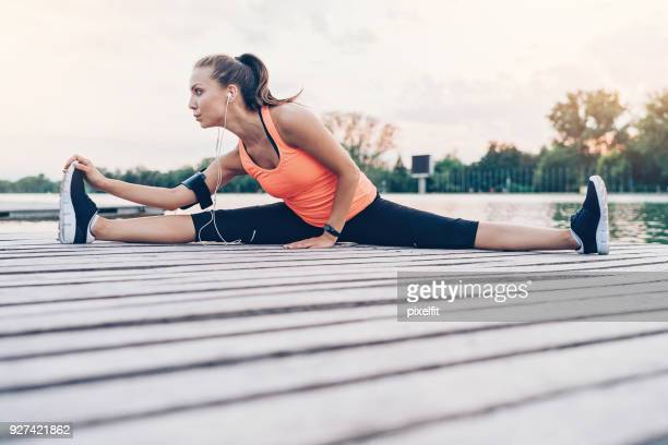 beautiful sportswoman making splits outdoors by the river - doing the splits stock photos and pictures